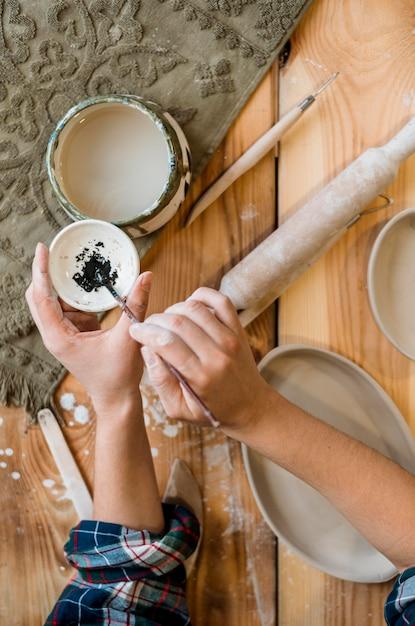 Donna che lavora nel suo laboratorio di ceramica Foto Gratuite