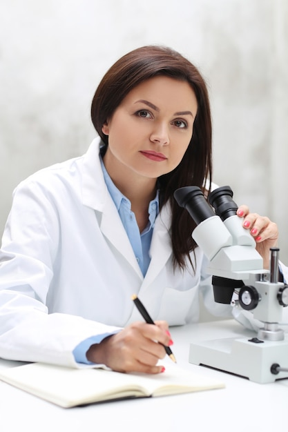 Woman working in the lab with a microscope Free Photo