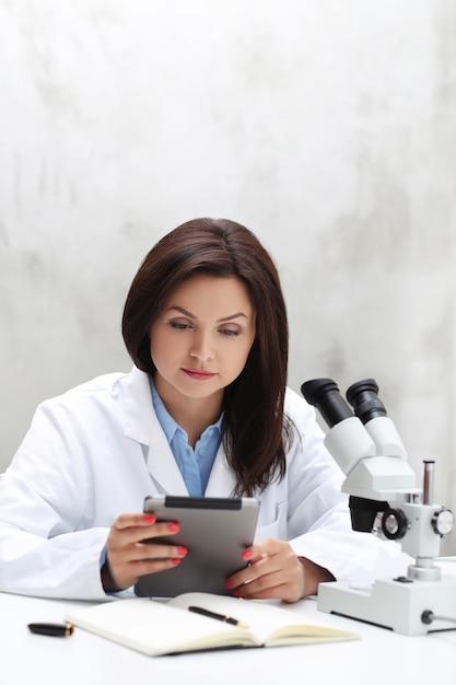 Donna che lavora in laboratorio con un microscopio Foto Gratuite