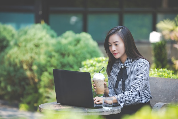Woman working on laptop in cafe and drinking coffee Free Photo