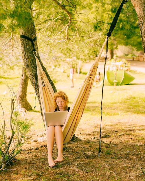 Woman working on laptop in hammock Free Photo