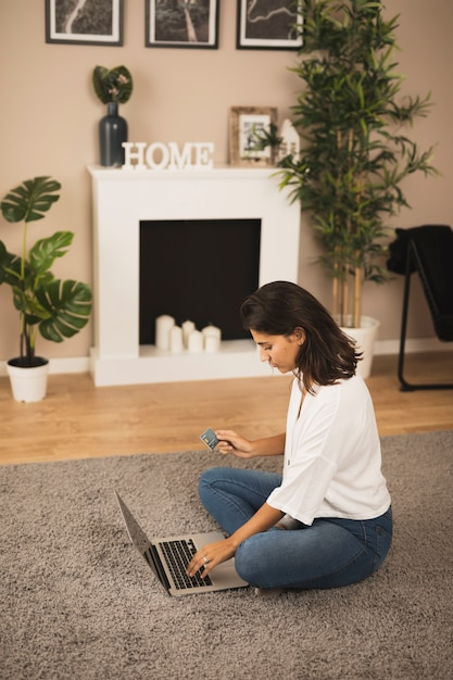 Woman working on laptop in living room Free Photo