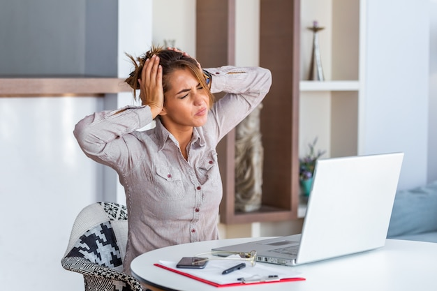 Woman working at office desk suffering from headache Premium Photo