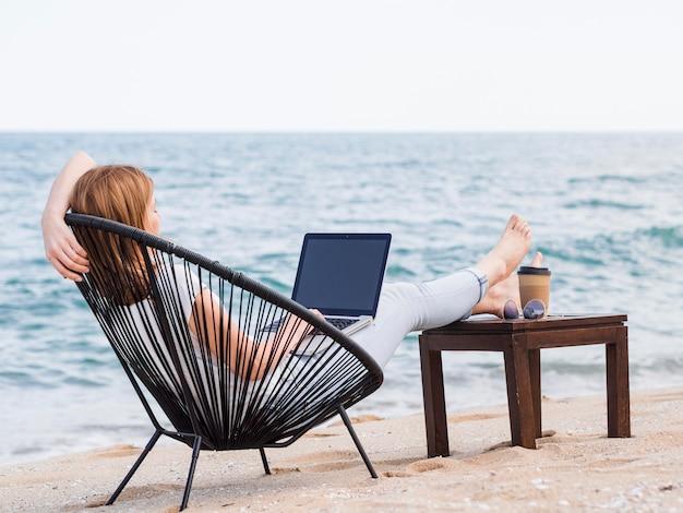ビーチチェアのラップトップで働く女性 Premium写真