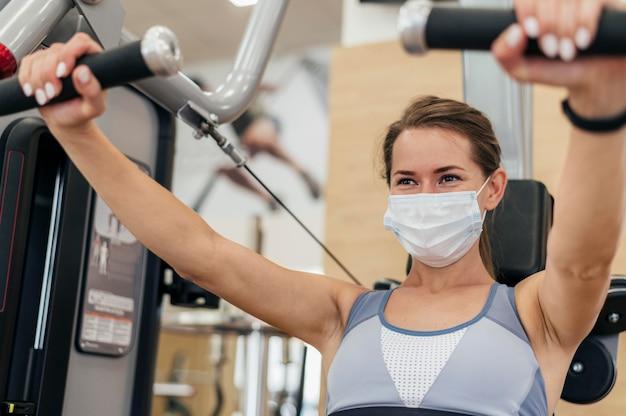 Женщина работает в тренажерном зале во время пандемии Бесплатные Фотографии