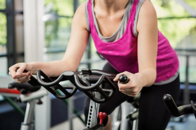 Woman working out on exercise bike at spinning class Premium Photo