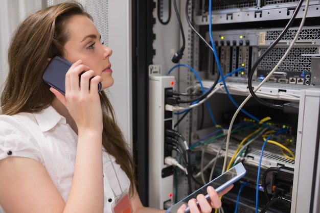 Woman working on servers with tablet pc on the phone Premium Photo