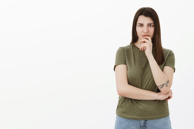 Donna preoccupata ed esitante come sentire qualcosa di inquietante pensando aggrottando le sopracciglia dalla preoccupazione e dall'intensa disapprovazione tenendo la mano sul labbro, considerando cosa fare, in piedi pensierosa e insicura sul muro grigio Foto Gratuite