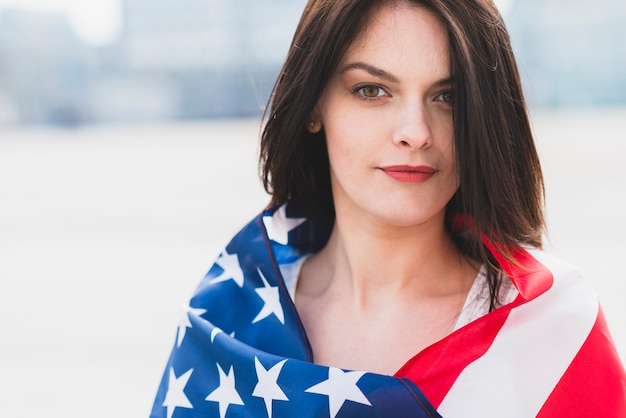 Woman wrapped in american flag patriotically looking at camera Free Photo
