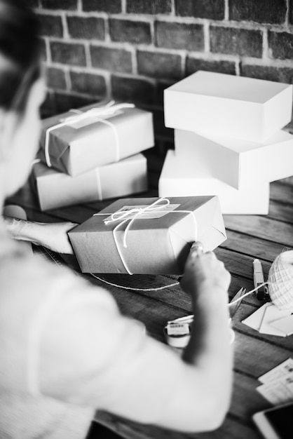 Woman wrapping a package by herself Free Photo