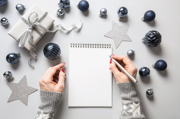 Woman writes goals, checklist, plans and dreams for new year. Premium Photo