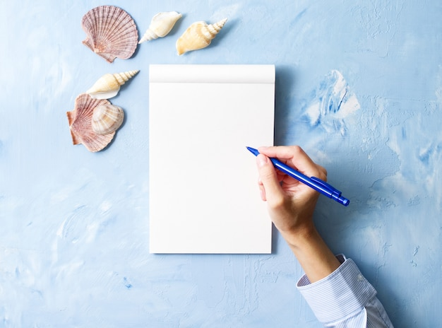 Woman writes in notebook on stone blue table,   frame of seashell, top view Premium Photo