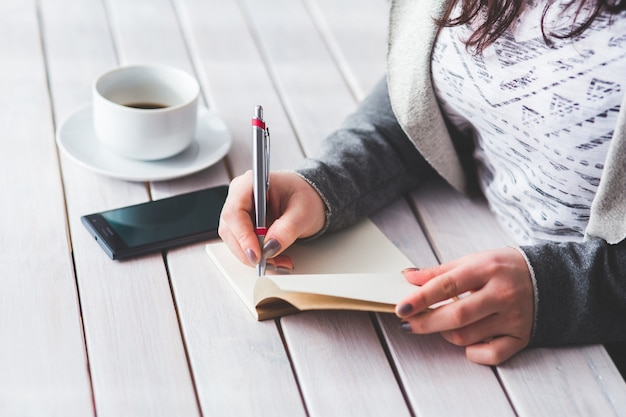 Woman writing in a diary Free Photo
