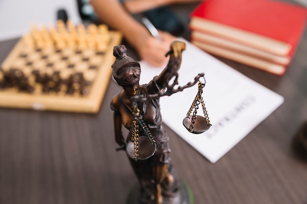 Woman writing in document at table with statue, books and chess Free Photo