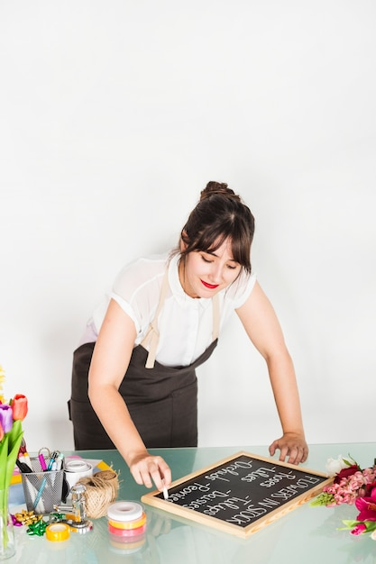 Woman writing flowers in stock on slate with chalk over desk Free Photo