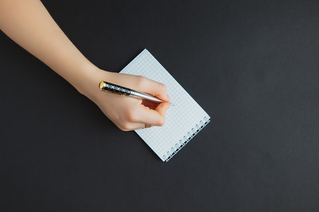 Woman writing in notepad at black table Premium Photo