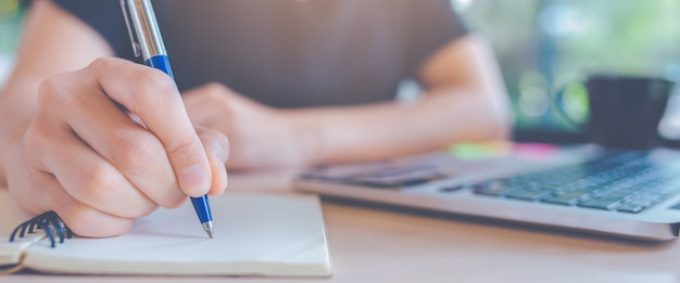 Woman writing on a notepad with a pen in office Premium Photo