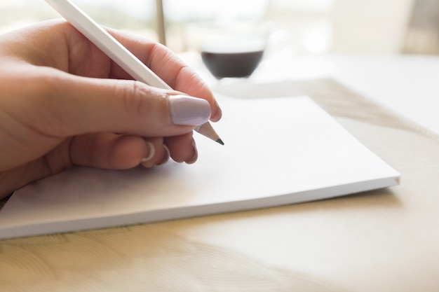 Woman writing in notepad Premium Photo