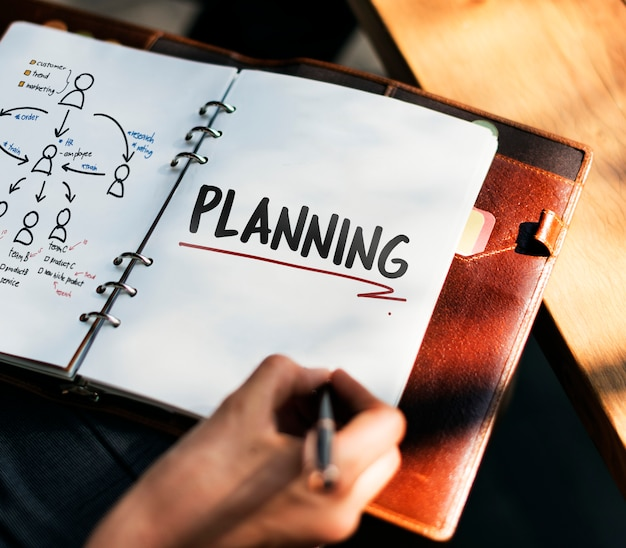 Woman writing and planning business strategy Free Photo