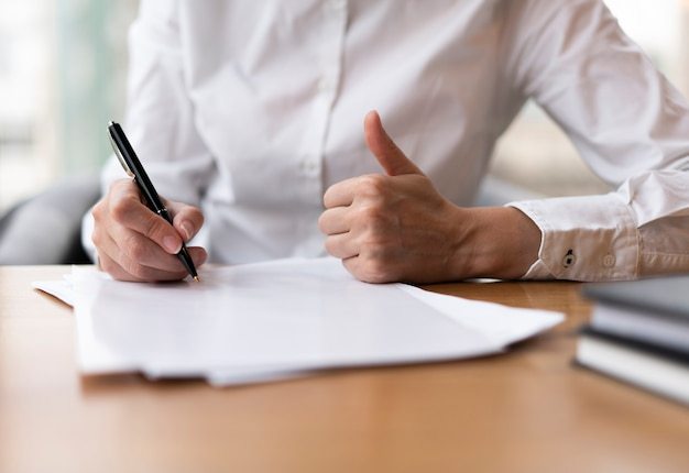Woman writing and showing thumbs up Free Photo