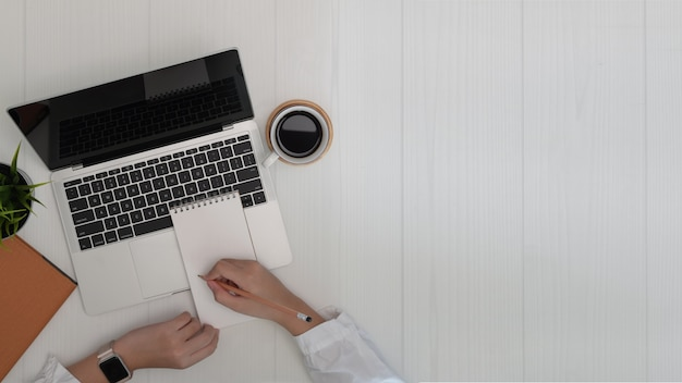 Woman writing and working on laptop. business and copy space background Premium Photo