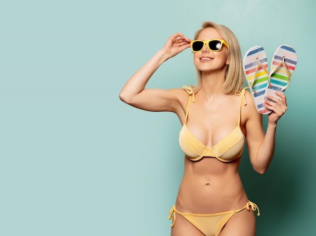 Woman in yellow bikini and sunglasses with flip-flops Premium Photo