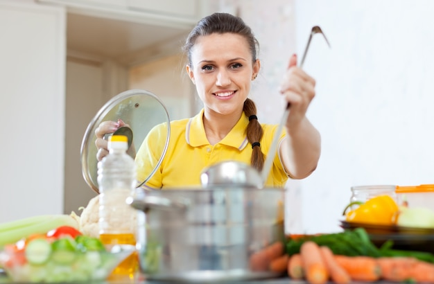 Woman in yellow cooking with ladle in saucepan Free Photo