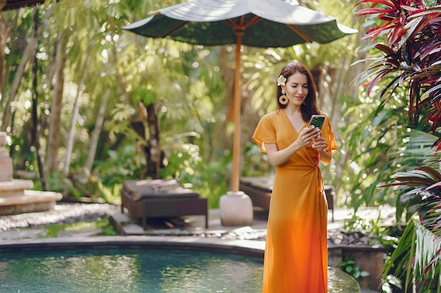 Woman in a yellow dress standing by the pool on a bali Free Photo