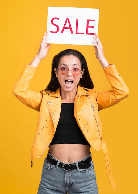Woman in yellow jacket being surprised about the sales Free Photo