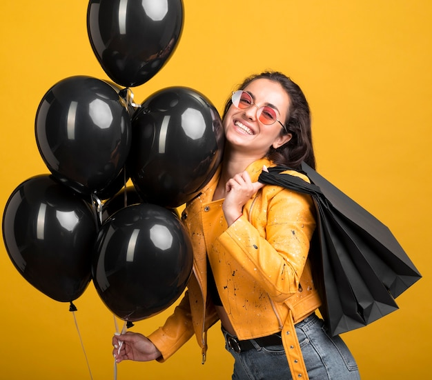 Woman in yellow jacket holding black friday balloons Free Photo