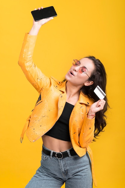Woman in yellow jacket holding her mobile phone in the air Free Photo