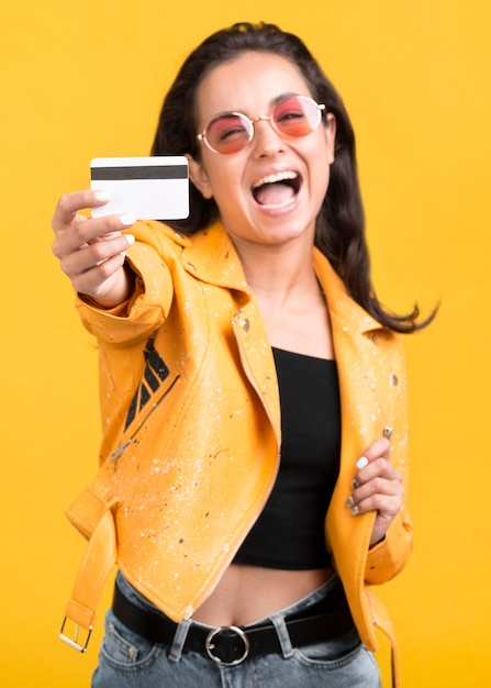 Woman in yellow jacket showing her shopping card Free Photo