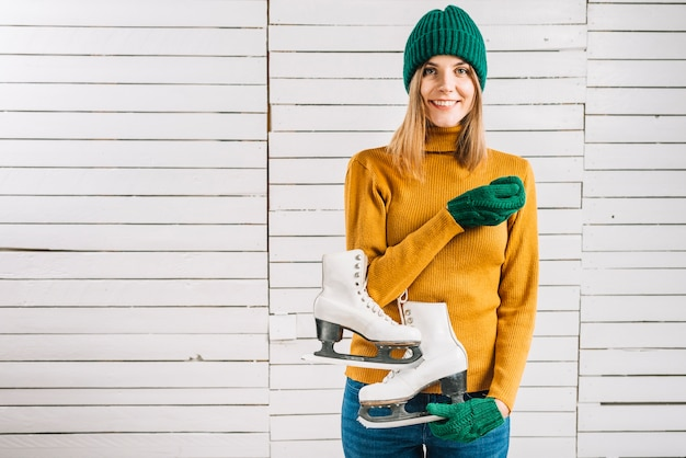 Woman in yellow sweater holding skates Free Photo