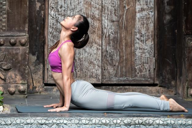 Woman in yoga exercises salutation to sun surya namaskar. Premium Photo