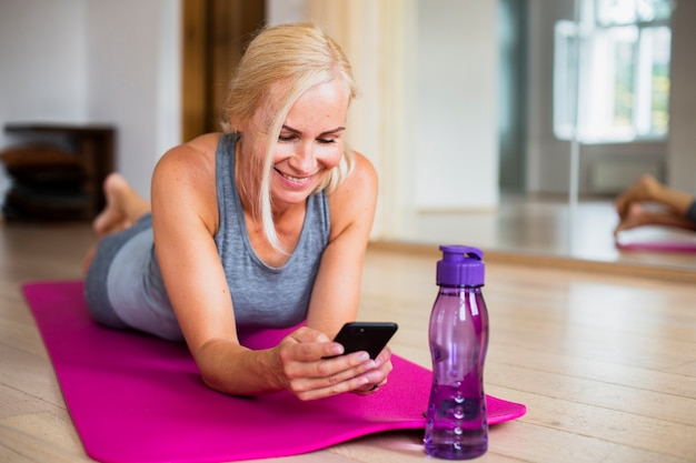 Woman on yoga mat checking her phone Free Photo