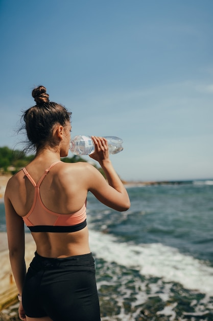 Woman in yoga outfit drinking fresh water from bottle after exercise on beach Free Photo