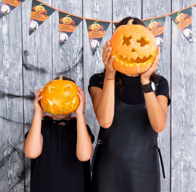 Woman and young boy holding carved pumpkins Free Photo