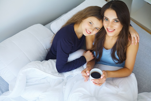 Woman and young girl lying in bed smiling Premium Photo