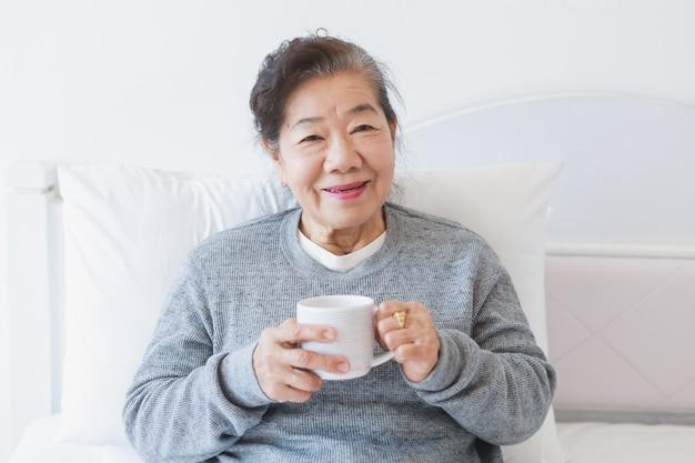 ベッドでコーヒーやお茶を飲んでアジアシニア老woman Premium写真