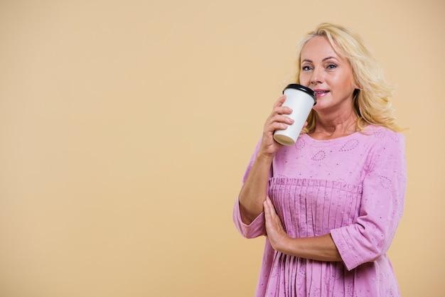 カメラを見てコーヒーのカップを持つ老woman 無料写真