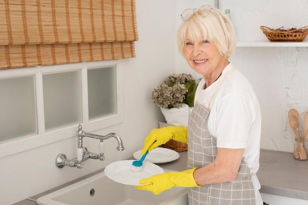 お皿を洗うスマイリー老woman 無料写真