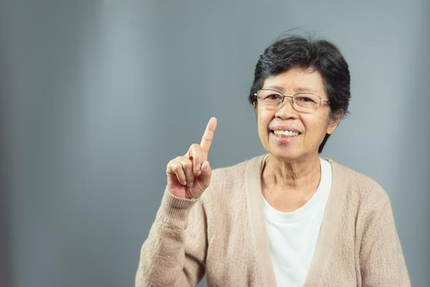 灰色のアイデアを考えて笑顔の老womanの肖像画 Premium写真