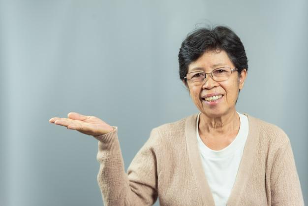 灰色の手でジェスチャーを示す笑みを浮かべて老womanの肖像画 Premium写真