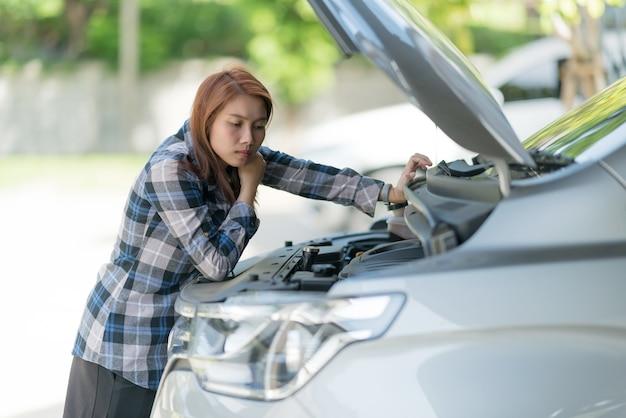 車のオイルレベルをチェックする女性、オイルカーを交換する Premium写真
