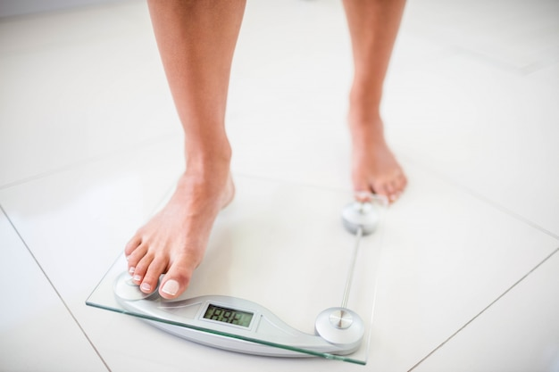 Womans feet going on weighting scale at home Premium Photo