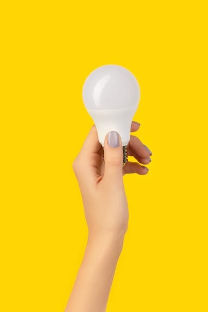 青い背景にled省エネ電球を持っている女性の手。持続可能なライフスタイル環境にやさしいコンセプト Premium写真