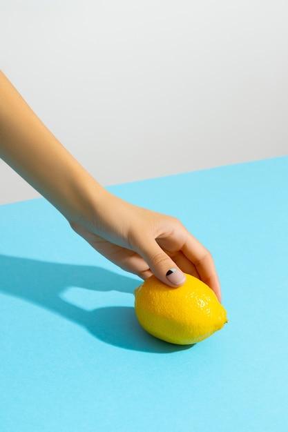 파란색 배경 위에 레몬을 들고여 대 손입니다. 최소한의 Slyle의 뷰티 패션 크리에이티브 레이아웃 프리미엄 사진