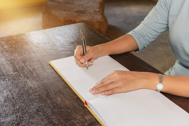 Womans hand signing a guest book with a pen Premium Photo