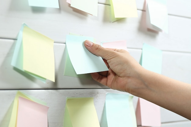 Womans hand sticking notepapers on white wooden board Free Photo