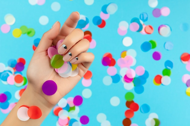Womans hand with colorful confetti over blue background. beauty fashion spa salon concept Premium Photo